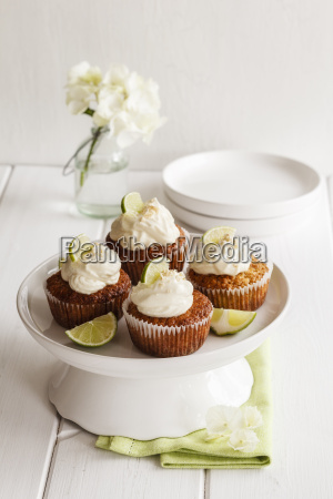 four lime cup cakes with cream
