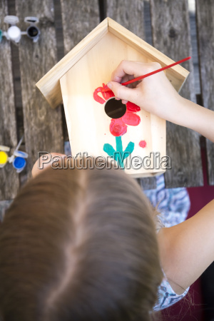 girl painting red flower on a