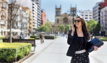 pretty young woman with smartphone walking