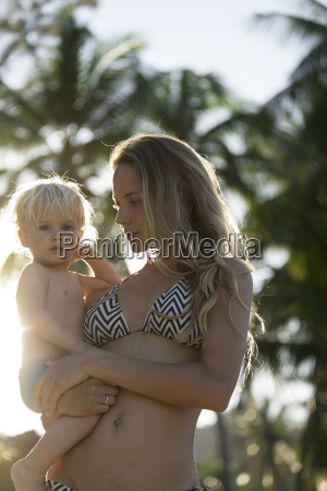 mother in bikini carrying son