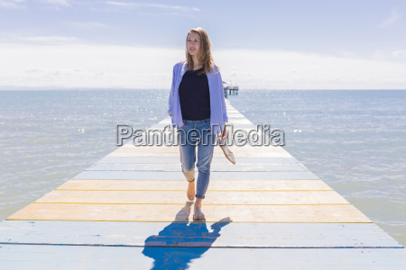 young woman walking on jetty