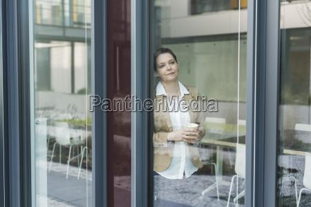 female senior manager standing on window