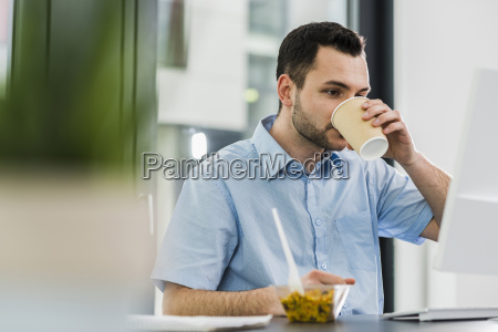 business man in office drinking coffee