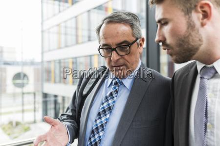 senior businessman talking to young businessman