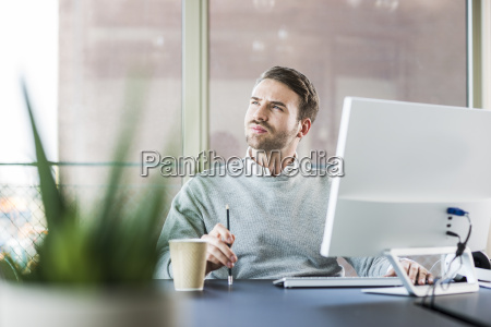 young man at office desk thinking
