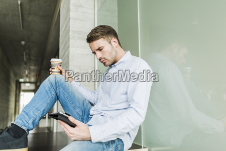 young man sitting on floor using