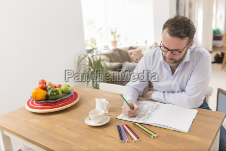man sitting at wooden table with