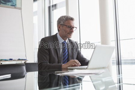 mature manager sitting in office using