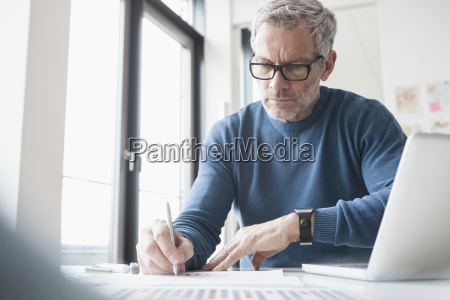 mature man sitting in office working