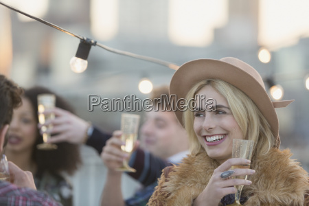 smiling young woman drinking champagne at