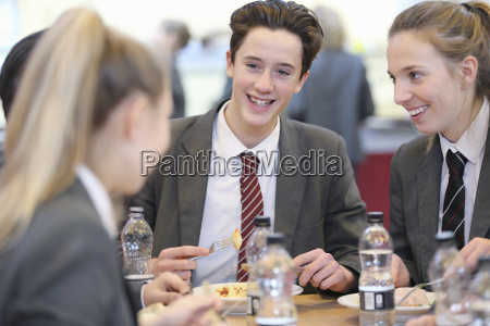 smiling high school students eating lunch