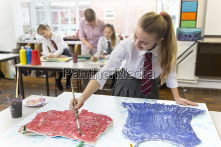 middle school student painting clothing on