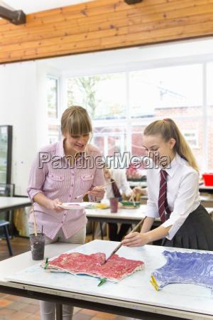 art teacher guiding middle school student