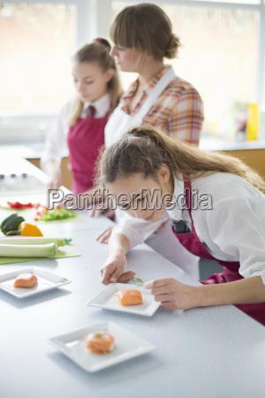 focused high school student plating food