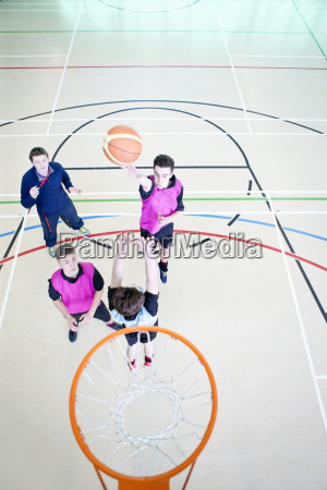 high school students playing basketball in