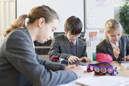 middle school students studying with digital