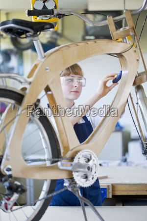 female high school student assembling bicycle
