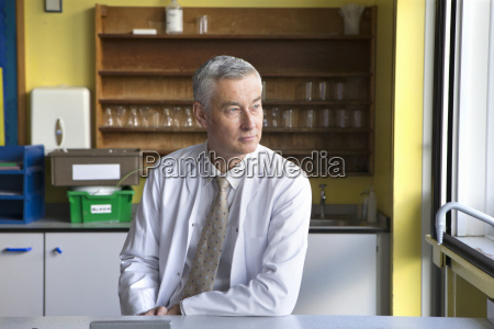 pensive science teacher looking out laboratory