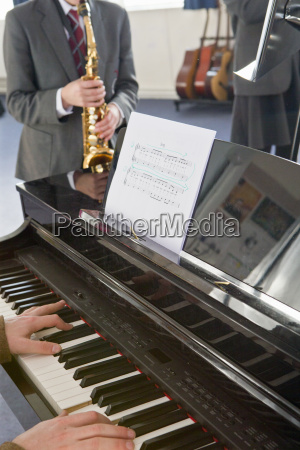 teacher playing piano with middle school