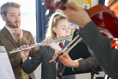 teacher teaching high school students playing