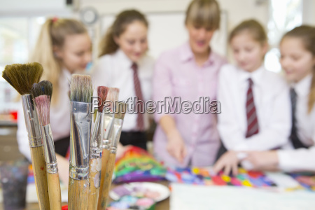 paintbrushes in foreground with art teacher