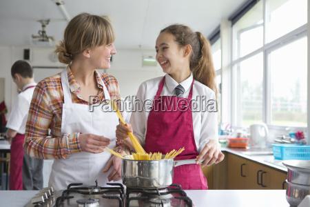smiling home economics teacher teaching high