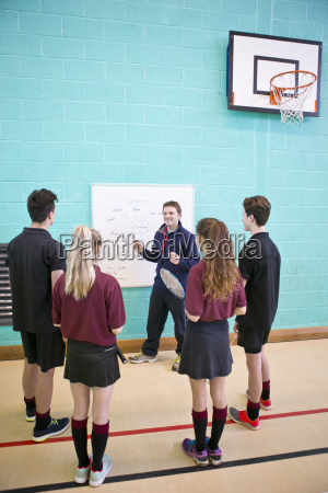 gym teacher at whiteboard teaching high