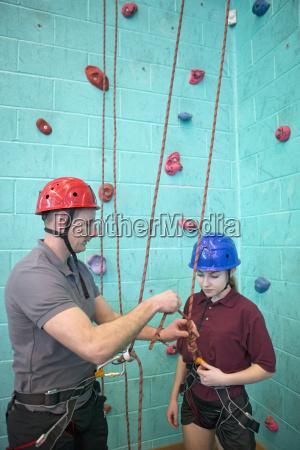 gym teacher preparing rock climbing safety
