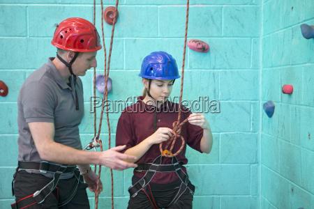 gym teacher teaching rock climbing safety