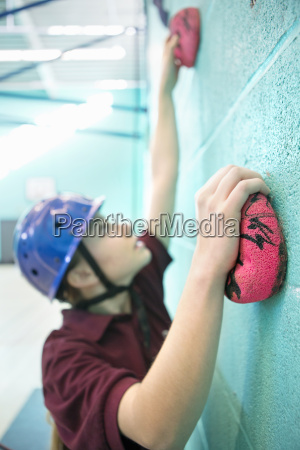 focused high school student climbing rock