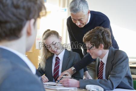 teacher helping high school students doing