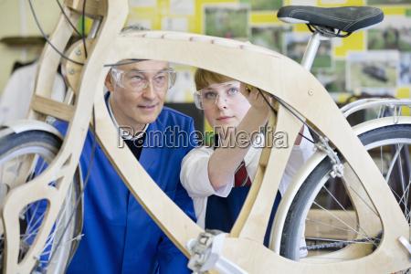 teacher teaching high school student assembling