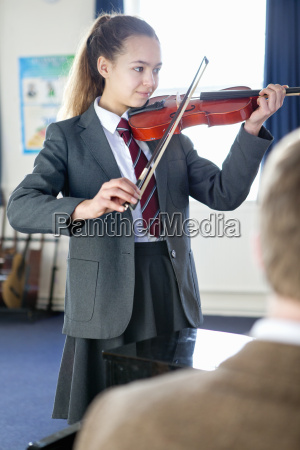 high school student playing violin in