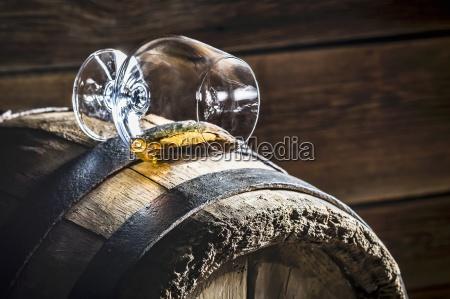 ein umgestuerztes glas cognac auf einem