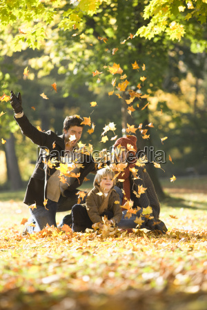 family tossing autumn leaves in park