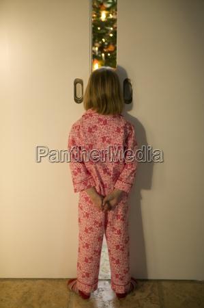 girl in pajamas peering though door