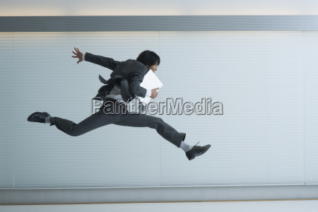 a businessman running with laptop in