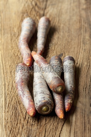 purple carrots on a wooden surface