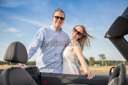 couple hugs the convertible and is
