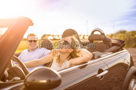 amorous couple in convertible goes on