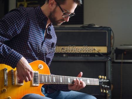 bearded man playing guitar