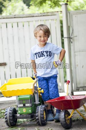 kleiner junge auf seinem spielzeug traktor