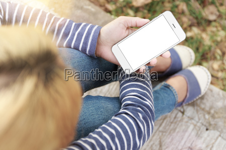 woman sitting and holding phone white