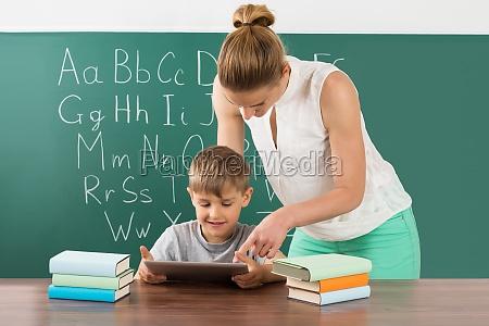 lehrer mit jungen mit digital tablette