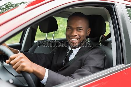 gluecklicher geschaeftsmann fahren auto