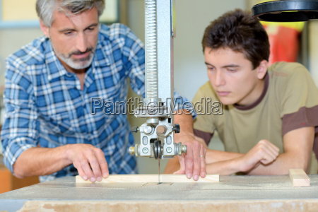 carpenter using a bench saw apprentice