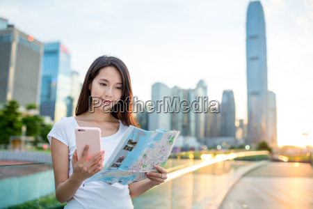 young woman using city map and