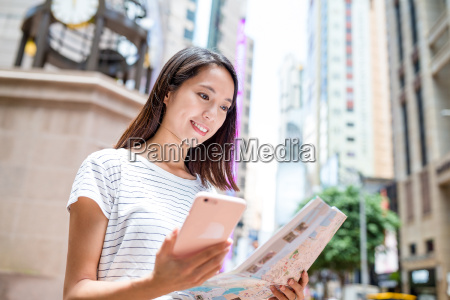 woman using city map and cellphone