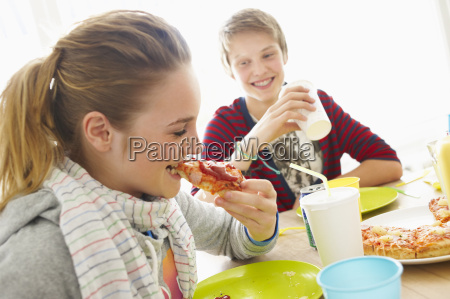 young boy and girl eating pizza