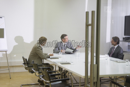 businessmen sitting at table in conference
